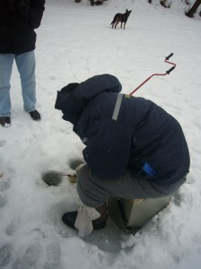 Pescando sobre el hielo a través de un agujero